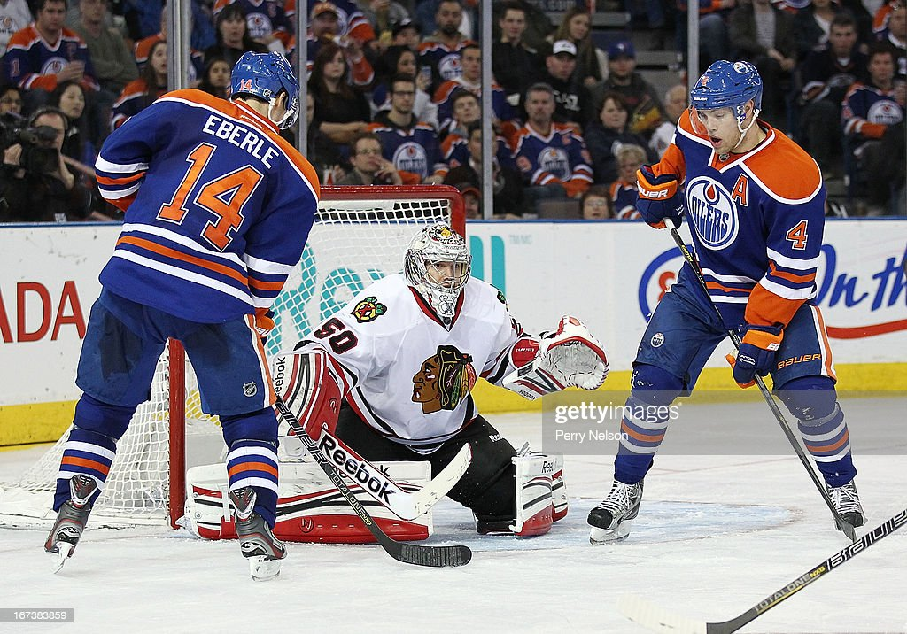 Jordan Eberle #14 and Taylor Hall #4 of the Edmonton Oilers flook for a rebound in front of Corey Crawford #50 of the Chicago Blackhawks at Rexall Place on April 24, 2013 in Edmonton, Alberta, Canada.