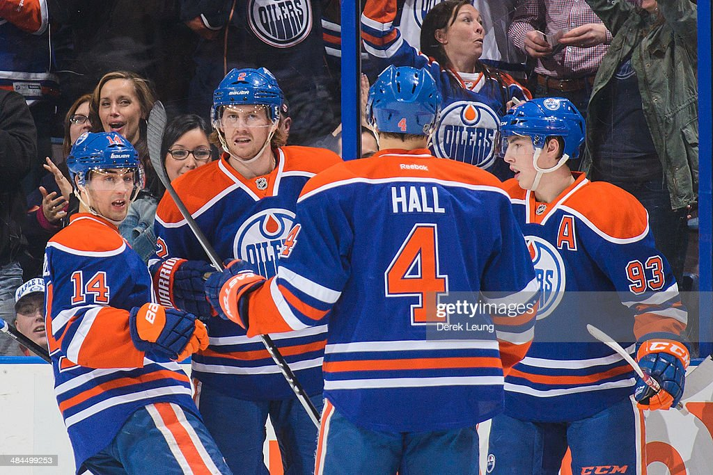 Jordan Eberle #14, Jeff Petry #2, Taylor Hall #4 and Ryan Nugent-Hopkins #93 of the Edmonton Oilers celebrate Petry's goal against the Vancouver Canucks during an NHL game at Rexall Place on April 12, 2014 in Edmonton, Alberta, Canada.