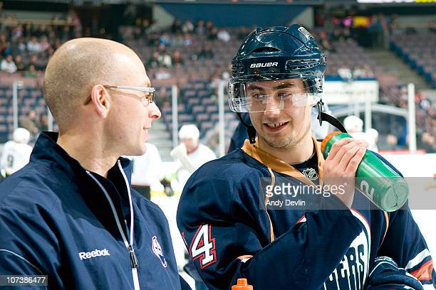 Jordan Eberle of the Edmonton Oilers chats with Chris Davie the Oilers' assistant medical trainer before a game against the Anaheim Ducks at Rexall...