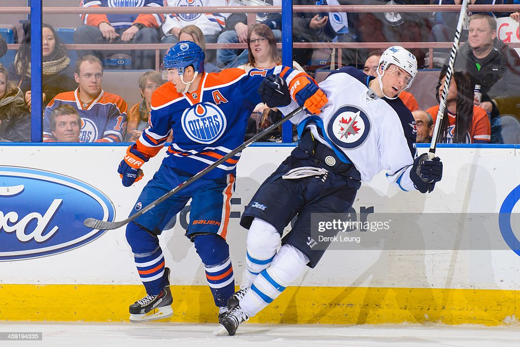 <a gi-track='captionPersonalityLinkClicked' href=/galleries/search?phrase=Jordan+Eberle&family=editorial&specificpeople=4898161 ng-click='$event.stopPropagation()'>Jordan Eberle</a> #14 of the Edmonton Oilers collides with <a gi-track='captionPersonalityLinkClicked' href=/galleries/search?phrase=Blake+Wheeler&family=editorial&specificpeople=716703 ng-click='$event.stopPropagation()'>Blake Wheeler</a> #26 of the Winnipeg Jets during an NHL game at Rexall Place on December 23, 2013 in Edmonton, Alberta, Canada. The Oilers defeated the Jets 6-2.