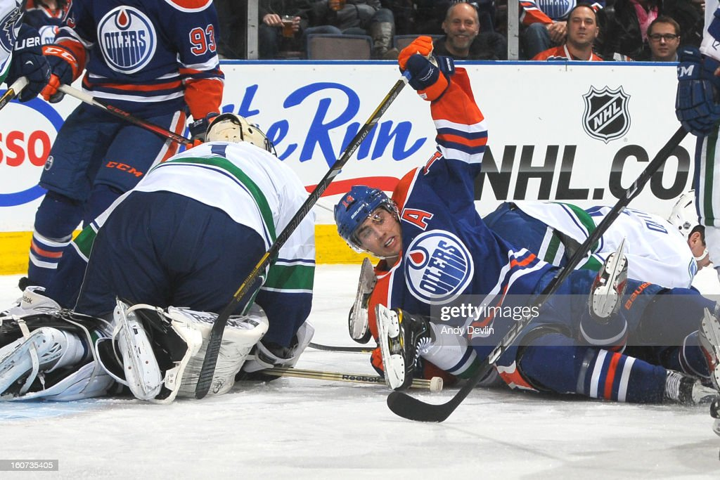 Jordan Eberle #14 of the Edmonton Oilers falls in front of the net in an NHL game against the Vancouver Canucks on February 4, 2013 at Rexall Place in Edmonton, Alberta, Canada.