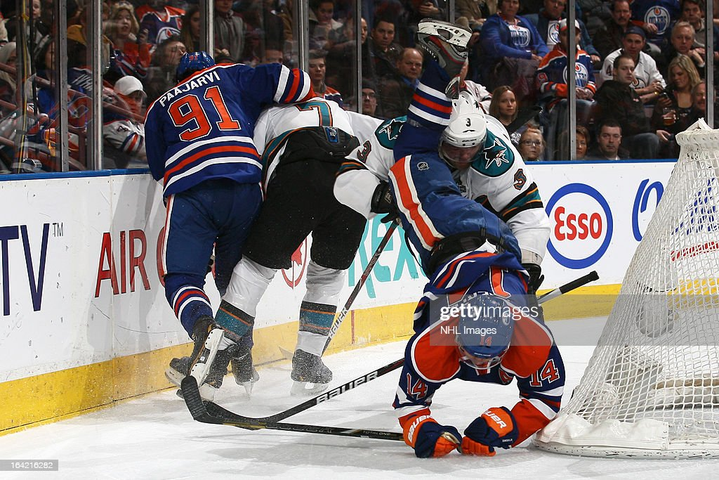 Jordan Eberle #14 of the Edmonton Oilers flips over Douglas Murray #3 of the San Jose Sharks as he battles for the puck behind the net on March 20, 2013 at Rexall Place in Edmonton, Alberta, Canada.