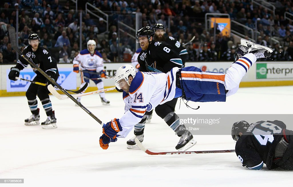 Jordan Eberle #14 of the Edmonton Oilers goes airborne after hitting Tomas Hertl #48 of the San Jose Sharks at SAP Center on March 24, 2016 in San Jose, California.