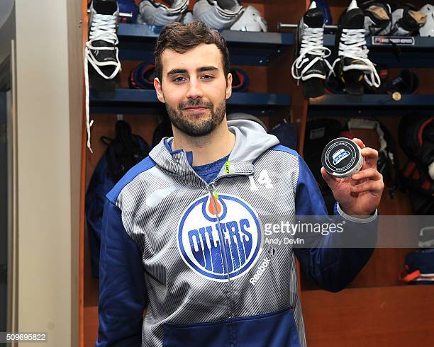 Jordan Eberle of the Edmonton Oilers holds a puck following the game in which he scored his first NHL hat trick against the Toronto Maple Leafs on...