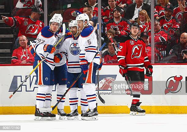 Jordan Eberle of the Edmonton Oilers is congratulated by his teammates after scoring a firstperiod goal as Reid Boucher of the New Jersey Devils...