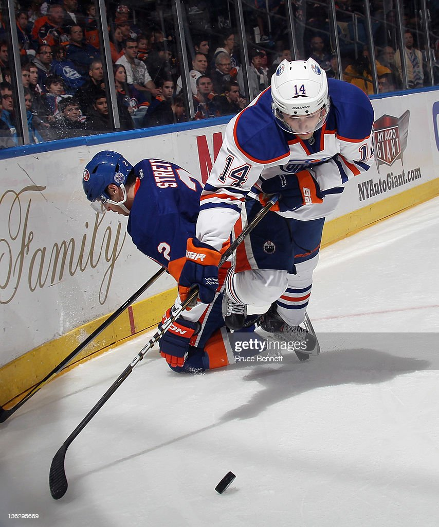 Jordan Eberle #14 of the Edmonton Oilers is tripped up by Mark Streit #2 of the New York Islanders at the Nassau Veterans Memorial Coliseum on December 31, 2011 in Uniondale, New York. The Islanders defeated the Oilers 4-1.