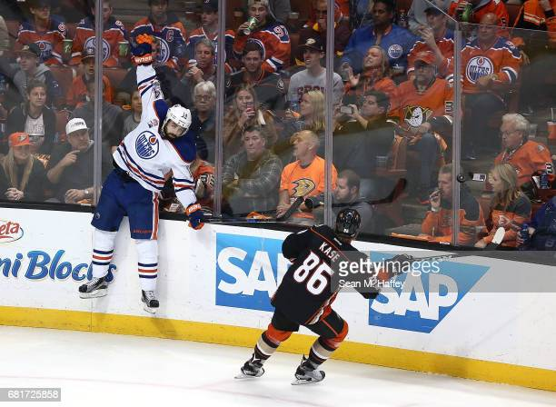 Jordan Eberle of the Edmonton Oilers leaps against the glass against Ondrej Kase of the Anaheim Ducks in Game Seven of the Western Conference Second...