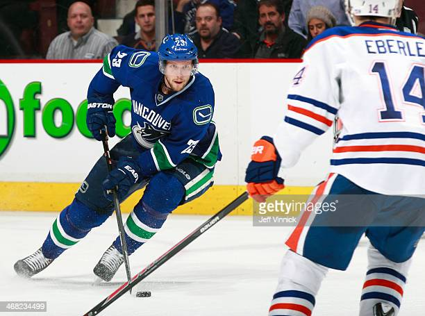 Jordan Eberle of the Edmonton Oilers looks on as Alexander Edler of the Vancouver Canucks skates up ice with the puck during their NHL game at Rogers...