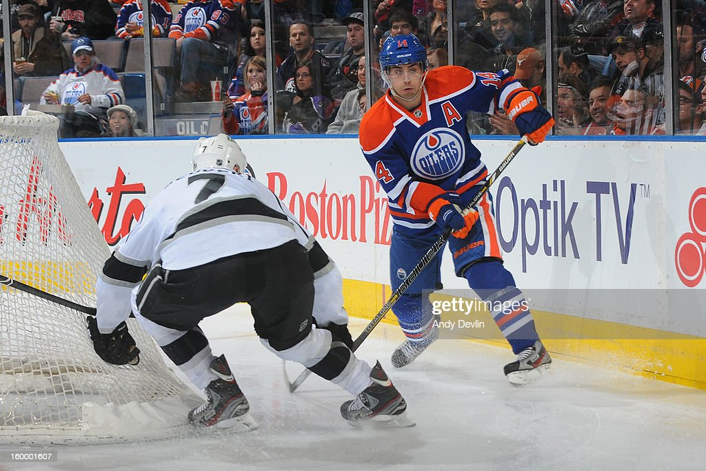 Jordan Eberle #14 of the Edmonton Oilers plays the puck from behind the net against Rob Scuderi #7 of the Los Angeles Kings at Rexall Place on January 24, 2013 in Edmonton, Alberta, Canada.