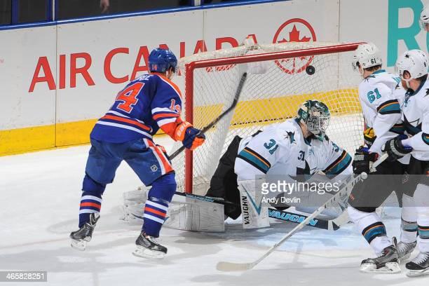 Jordan Eberle of the Edmonton Oilers scores a goal on Antti Niemi of the San Jose Sharks on January 29 2014 at Rexall Place in Edmonton Alberta Canada
