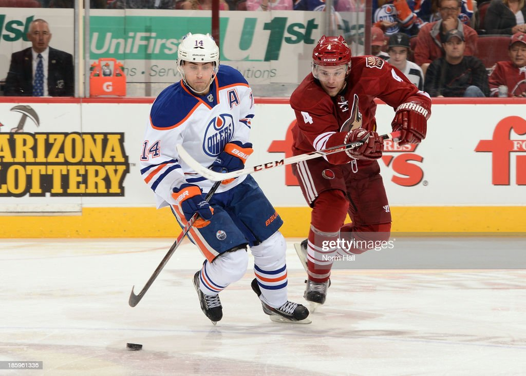 <a gi-track='captionPersonalityLinkClicked' href=/galleries/search?phrase=Jordan+Eberle&family=editorial&specificpeople=4898161 ng-click='$event.stopPropagation()'>Jordan Eberle</a> #14 of the Edmonton Oilers skates the puck up ice while being defended by <a gi-track='captionPersonalityLinkClicked' href=/galleries/search?phrase=Zbynek+Michalek&family=editorial&specificpeople=243230 ng-click='$event.stopPropagation()'>Zbynek Michalek</a> #4 of the Phoenix Coyotes at Jobing.com Arena on October 26, 2013 in Glendale, Arizona.