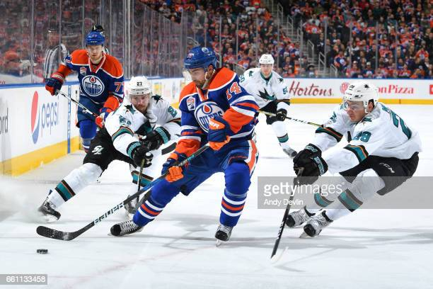 Jordan Eberle of the Edmonton Oilers skates with the puck while being pursued by Joonas Donskoi and Timo Meier of the San Jose Sharks on March 30...