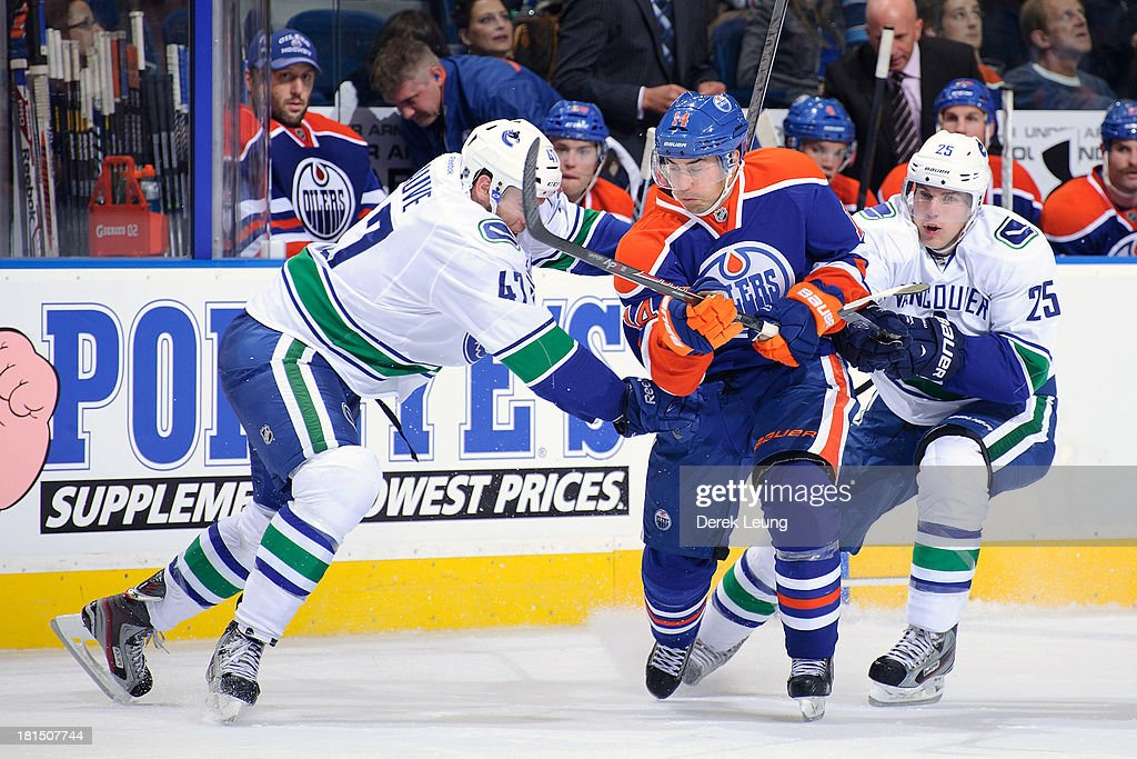 <a gi-track='captionPersonalityLinkClicked' href=/galleries/search?phrase=Jordan+Eberle&family=editorial&specificpeople=4898161 ng-click='$event.stopPropagation()'>Jordan Eberle</a> #14 of the Edmonton Oilers splits the defense of Yann Sauve #47 and <a gi-track='captionPersonalityLinkClicked' href=/galleries/search?phrase=Mike+Santorelli&family=editorial&specificpeople=4517042 ng-click='$event.stopPropagation()'>Mike Santorelli</a> #25 of the Vancouver Canucks during a preseason NHL game at Rexall Place on September 21, 2013 in Edmonton, Alberta, Canada.