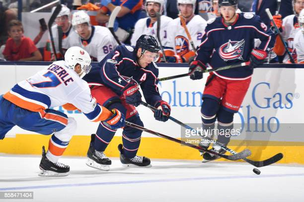 Jordan Eberle of the New York Islanders attempts to knock the puck away from Jack Johnson of the Columbus Blue Jackets during the third period of a...