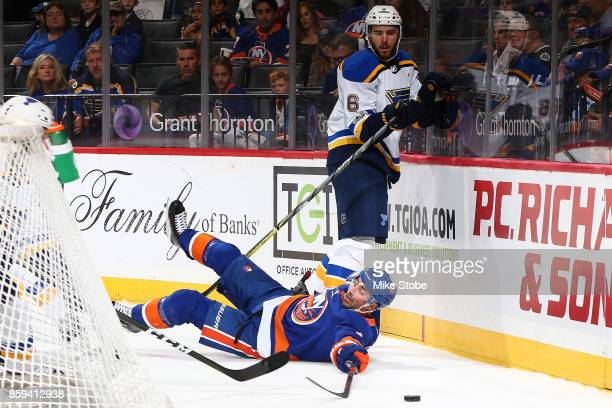 Jordan Eberle of the New York Islanders falls to the ice battling for the puck agaiinst Joel Edmundson of the St Louis Blues at Barclays Center on...