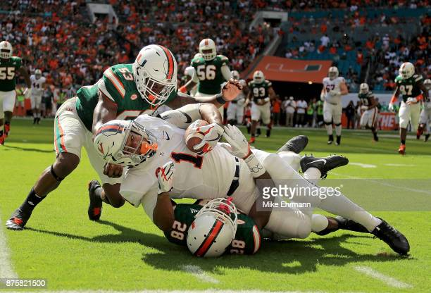 Jordan Ellis of the Virginia Cavaliers makes a catch over Michael Jackson of the Miami Hurricanes during a game at Hard Rock Stadium on November 18...