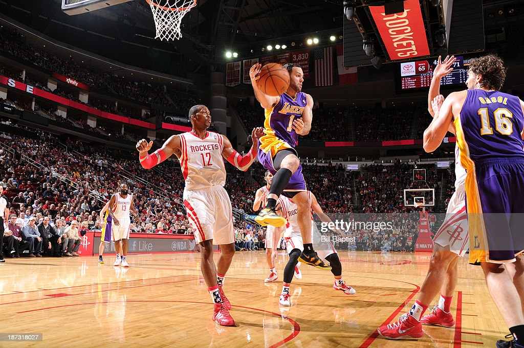 Jordan Farmar #1 of the Los Angeles Lakers passes in mid-air against the Houston Rockets on November 7, 2013 at the Toyota Center in Houston, Texas.