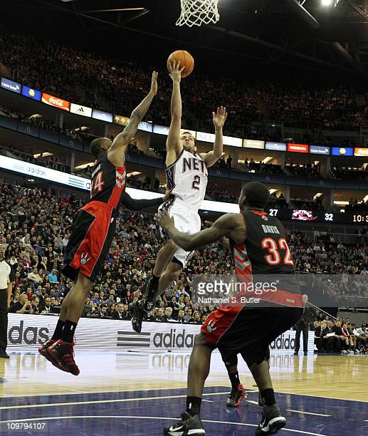 Jordan Farmar of the New Jersey Nets shoots against Sonny Weems and Ed Davis of the Toronto Raptors during their game at the O2 Arena on March 5 2011...