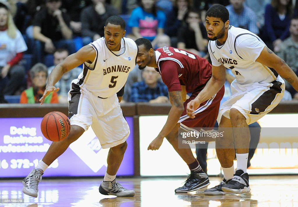 Jordan Gathers of the St Bonaventure Bonnies reaches for a loose ball in front of Clyde Santee of the Massachusetts Minutemen and Chris Dees of the...