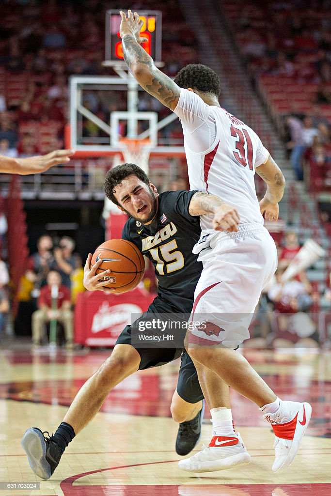 Jordan Geist #15 of the Missouri Tigers tries to drive around and is fouled by Anton Beard #31 of the Arkansas Razorbacks at Bud Walton Arena on January 14, 2017 in Fayetteville, Arkansas. The Razorbacks defeated the Tigers 92-73.