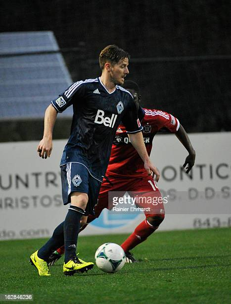 Jordan Harvey of the Vancouver Whitecaps FC looks to pass as Patrick Nyarko of the Chicago Fire defends during the first half of the Carolina...