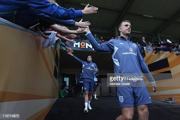 Jordan Henderson and Phil Jones high five local schoolkids as they walk out from the dressing rooms during the England U21's training session at...