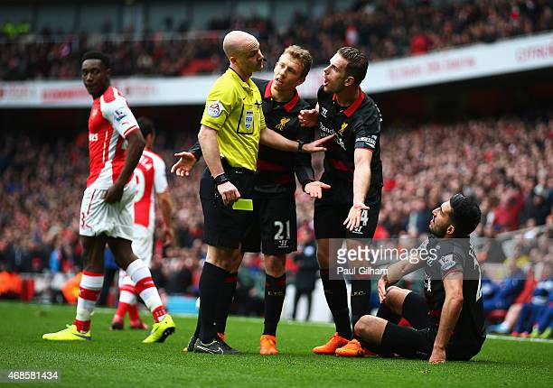 Jordan Henderson of Liverpool and Lucas Leiva of Liverpool argue with referee Anthony Taylor as Emre Can of Liverpool sits on the turf during the...