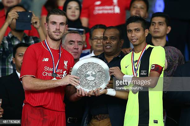 Jordan Henderson of Liverpool and Mohd Razman of Malaysia XI lift up the joint winners trophy after they drew 11 during the international friendly...