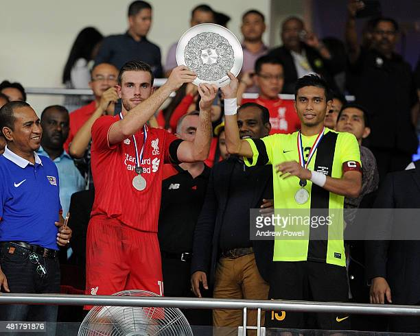 Jordan Henderson of Liverpool and Mohd Razman Roslan of Malaysia XI lifting the trophy at the end the international friendly match between Malaysia...