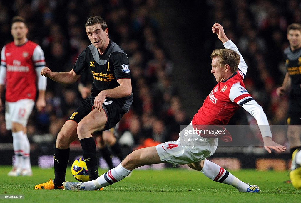 Jordan Henderson of Liverpool brought down by Per Mertesacker of Arsenal during the Barclays Premier League match between Arsenal and Liverpool at Emirates Stadium on January 30, 2013 in London, England.