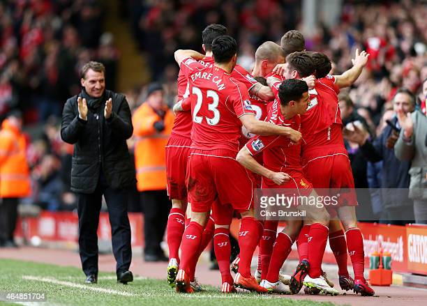 Jordan Henderson of Liverpool celebrates with teammates after scoring the opening goal during the Barclays Premier League match between Liverpool and...