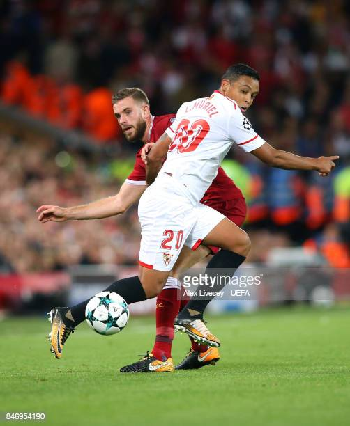 Jordan Henderson of Liverpool FC challenges Luis Muriel of Sevilla FC during the UEFA Champions League group E match between Liverpool FC and Sevilla...