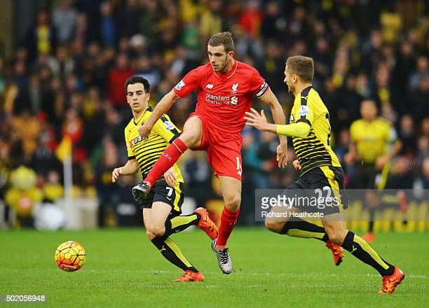 Jordan Henderson of Liverpool is watched by Jose Manuel Jurado and Almen Abdi of Watford during the Barclays Premier League match between Watford and...