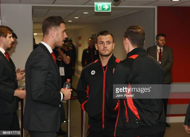 Jordan Henderson of Liverpool talks with Jack Wilshere and Brad Smith of AFC Bournemouth before the Premier League match between Liverpool and AFC...