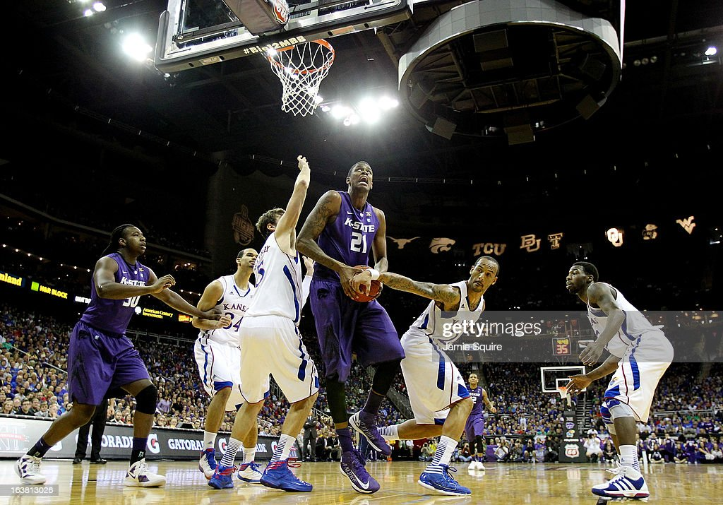 Jordan Henriquez #21 of the Kansas State Wildcats struggles to shoot against Jeff Withey #5 and Travis Releford #24 of the Kansas Jayhawks in the first half during the Final of the Big 12 basketball tournament at Sprint Center on March 16, 2013 in Kansas City, Missouri.