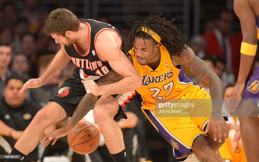 Jordan Hill (R) of the Los Angeles Lakers tangles with Joel Freeland (L) of the Portland Trail Blazers during their NBA game on December 28, 2012 at Staples Center in Los Angeles, California. The Lakers rolled over the Blazers 104-87. AFP PHOTO / Joe KLAMAR