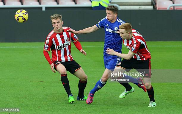 Jordan Houghton of Chelsea goes through the gap between Martin Smith and Duncan Watmore during the Barclays U21 Premier League match between...