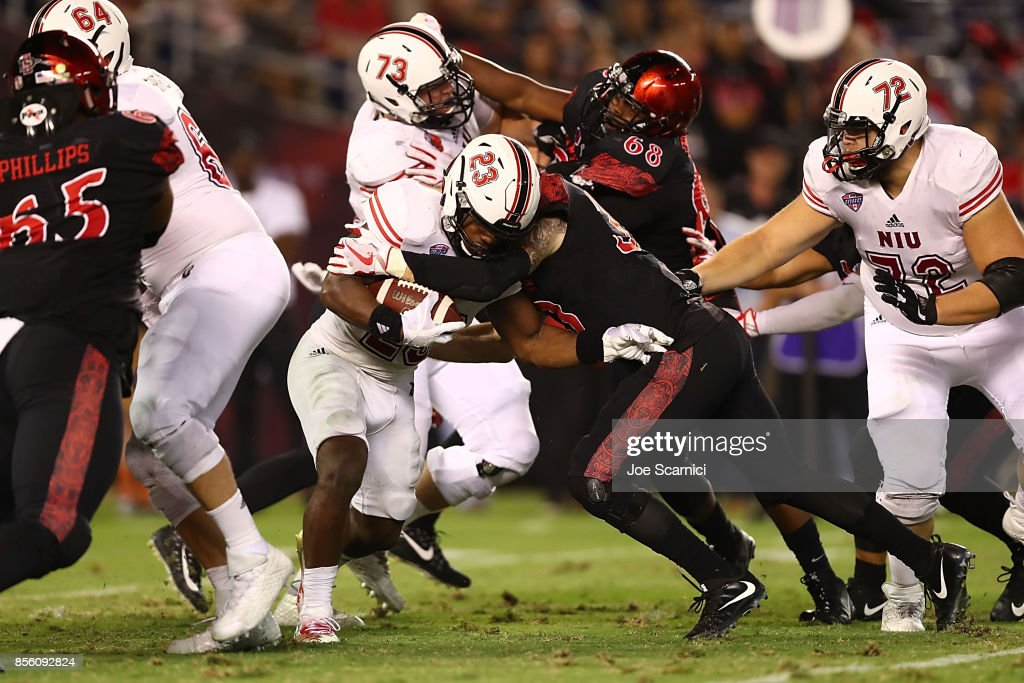 Jordan Huff #23 of the Northern Illinois Huskies is tackled in the second quarter during the Northern Illinois v San Diego State game at Qualcomm Stadium on September 30, 2017 in San Diego, California.