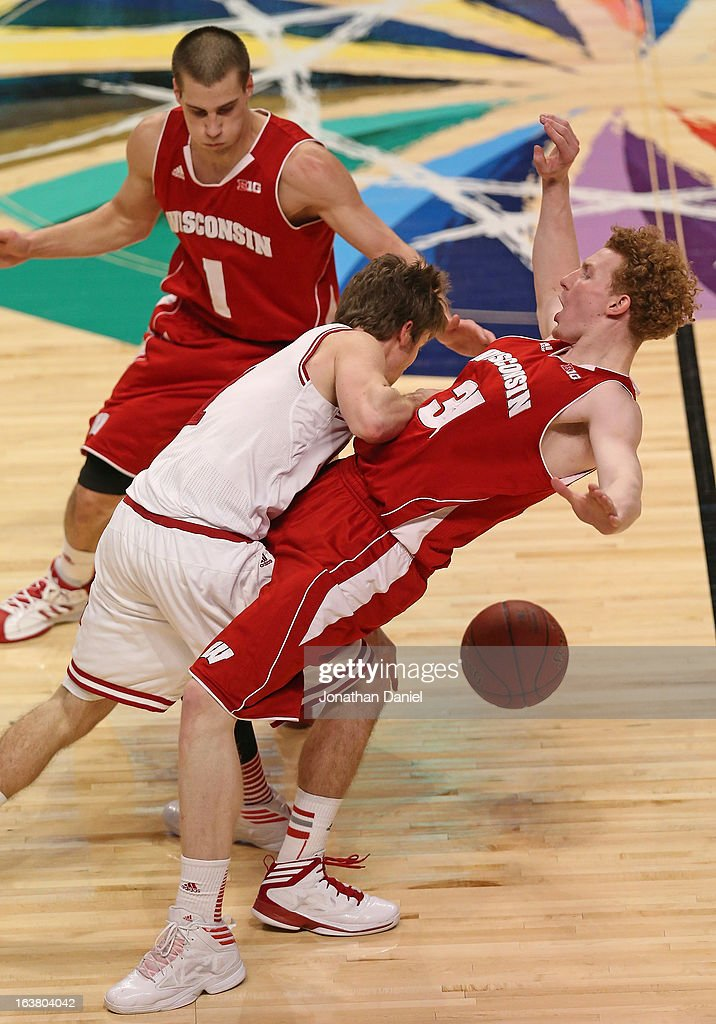 Jordan Hulls #1 of the Indiana Hoosiers charges into Mike Bruesewitz #31 of the Wisconsin Badgers, as Ben Brust #1 of the Badgers watches from behind, during a semifinal game of the Big Ten Basketball Tournament at the United Center on March 16, 2013 in Chicago, Illinois.