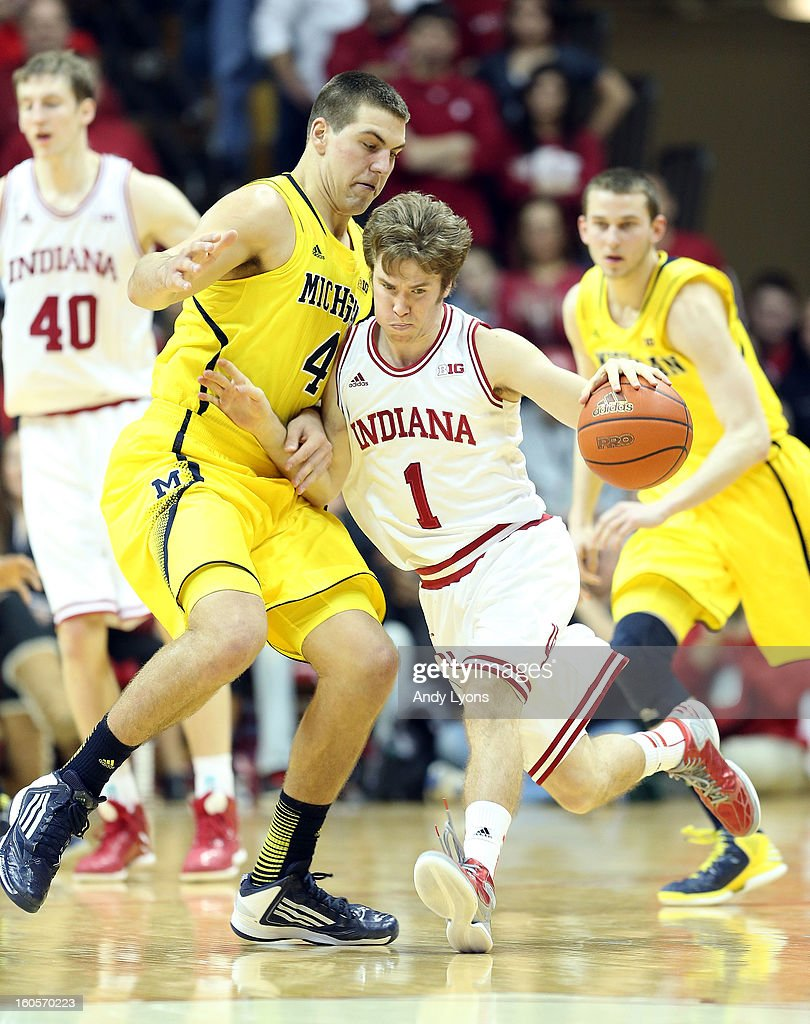 Jordan Hulls #1 of the Indiana Hoosiers dribbles the ball while defended by Mitch McGary #4 of the Michigan Wolverines during the game at Assembly Hall on February 2, 2013 in Bloomington, Indiana.