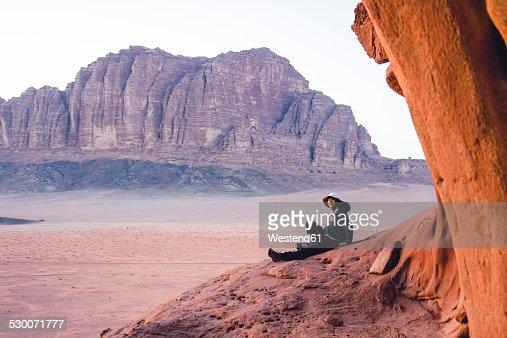 Jordan, Japanese woman sitting on top of a rock in Wadi Rum