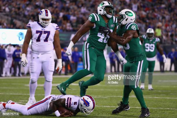 Jordan Jenkins of the New York Jets celebrates with teammate outside linebacker Josh Martin after sacking quarterback Tyrod Taylor of the Buffalo...
