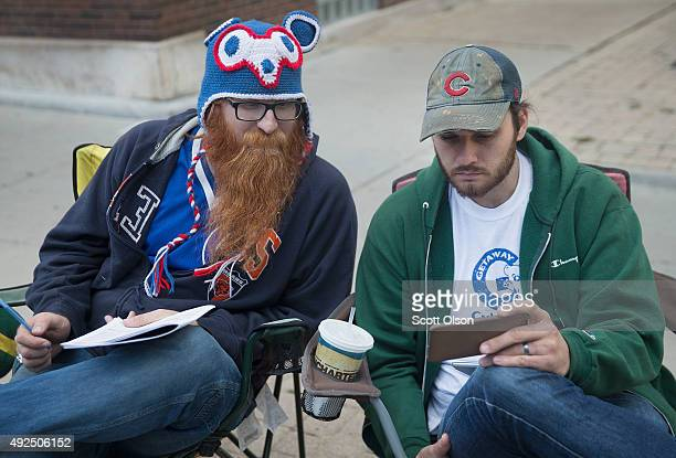 Jordan Klint and Devin Sullivan watch the game on a cell phone on the sidewalk across from Wrigley Field as the Chicago Cubs play the St Louis...