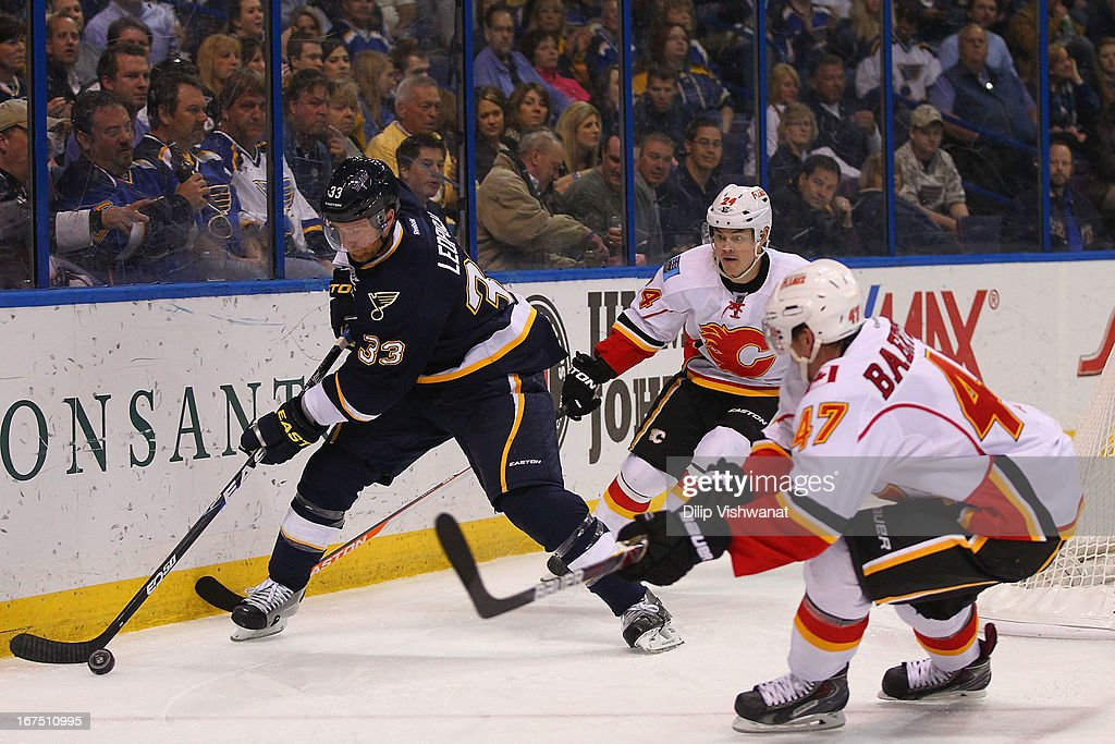 Jordan Leopold #33 of the St. Louis Blues picks up a loose puck against Sven Baertschi #47 and Jiri Hudler #24 both of the Calgary Flames during the second period at the Scottrade Center on April 25, 2013 in St. Louis, Missouri.