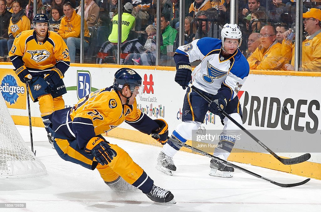 Jordan Leopold #33 of the St. Louis Blues plays the puck behind the net against Patric Hornqvist #27 of the Nashville Predators at Bridgestone Arena on October 26, 2013 in Nashville, Tennessee.