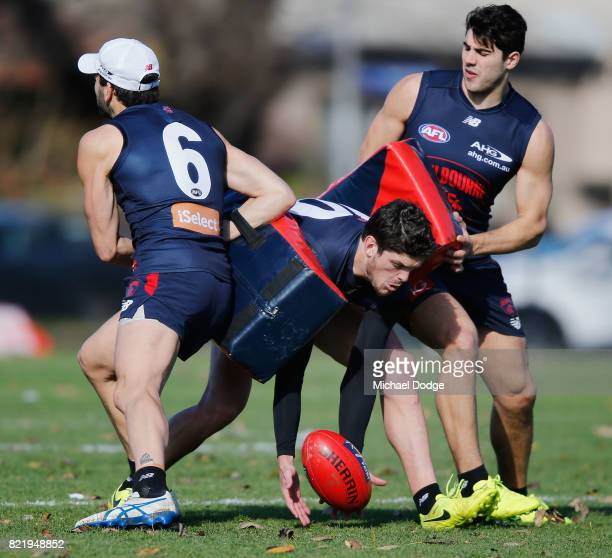 Jordan Lewis of the Demons and Christian Petracca put pressure on Angus Brayshaw during a Melbourne Demons AFL training session at Gosch's Paddock on...