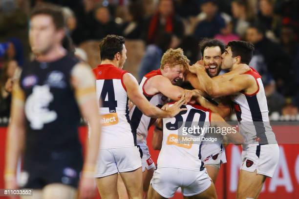 Jordan Lewis of the Demons celebrates a goal after the final siren wit teammates during the round 16 AFL match between the Carlton Blues and the...