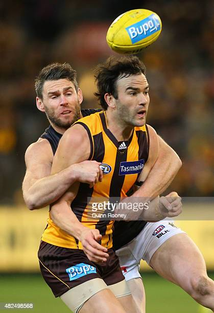 Jordan Lewis of the Hawks handballs whilst being tackled by Chris Newman of the Tigers during the round 18 AFL match between the Hawthorn Hawks and...