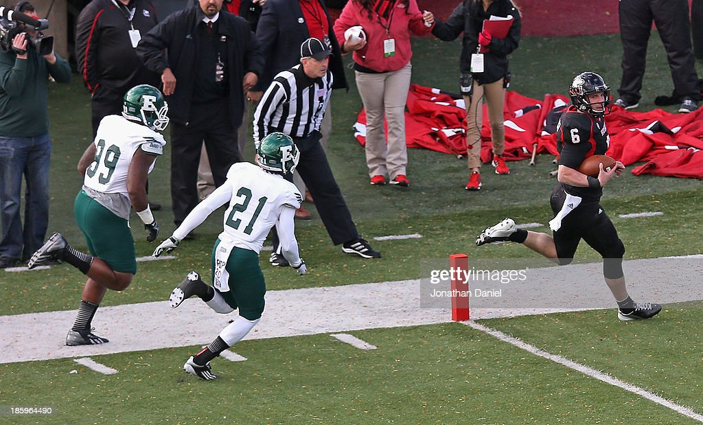 Jordan Lynch #6 of the Northern Illinois Huskies scores a touchdown in front of Ja'Ron Gillespie #21 and Aaron Pipkins #99 of the Eastern Michigan Eagles at Brigham Field on October 26, 2013 in DeKalb, Illinois. Northern Illinois defeated Eastern Michigan 59-20.