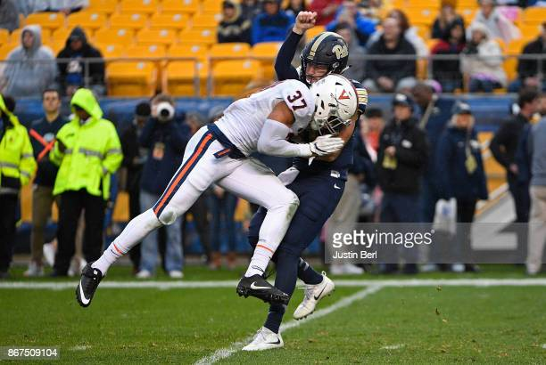 Jordan Mack of the Virginia Cavaliers hits Ben Dinucci of the Pittsburgh Panthers after a throw in the first half during the game at Heinz Field on...